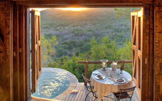 Blick von einer Terrasse mit Erfrischungspool auf das malerische Phinda Game Reserve bei Sonnenuntergang