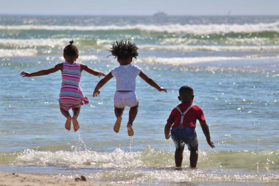 Children jumping in waves in South Africa