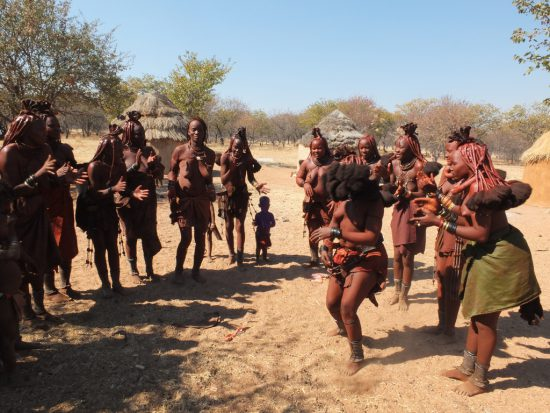 Himba aus Namibia in traditioneller Kleidung beim Tanzen