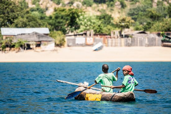 Two boys canoeing in Lake Malawi