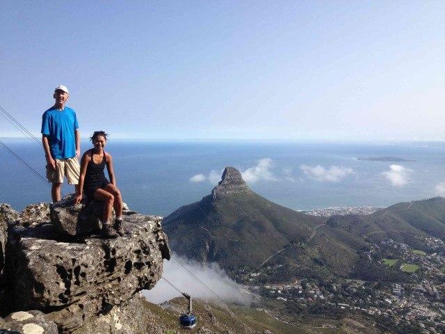 Zwei Wanderer auf der Spitze des Tafelbergs mit dem Lion's Head und dem Zentrum von Kapstadt im Hintergrund