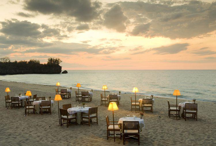 Auf einem Strand stehen viele Tische und Sesseln, daneben das Meer