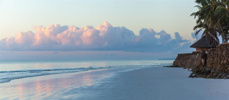 Ein Strand mit Palmen und Wolken in Kenia