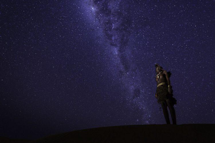 Eine Person starrt in den tiefblauen Sternenhimmel