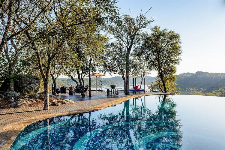 Ein Pool auf einer Terrasse, dahinter der Wald