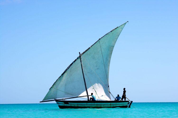 Ein Segelboot mit drei Personen im Wasser, dahinter blauer Himmel