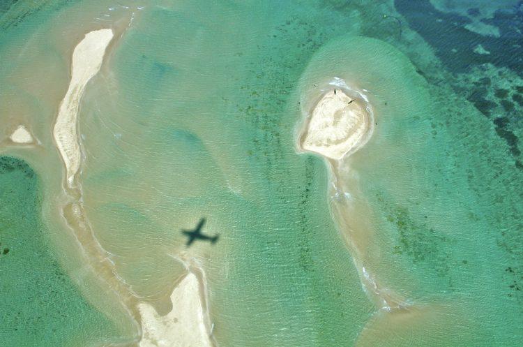 eine Aufnahme von oben: im Meer ein Schatten eines Flugzeuges