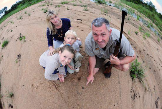 Guide mit Gewehr, zwei Kinder und Mutter blicken in die Kamera