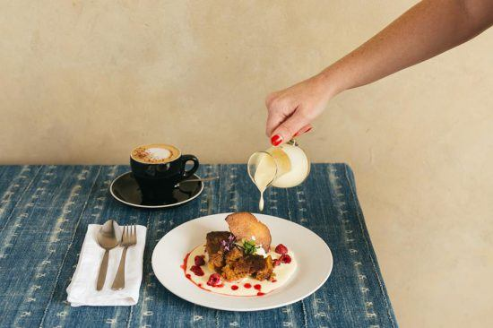 Frau gießt Vanillesoße über Malva Pudding