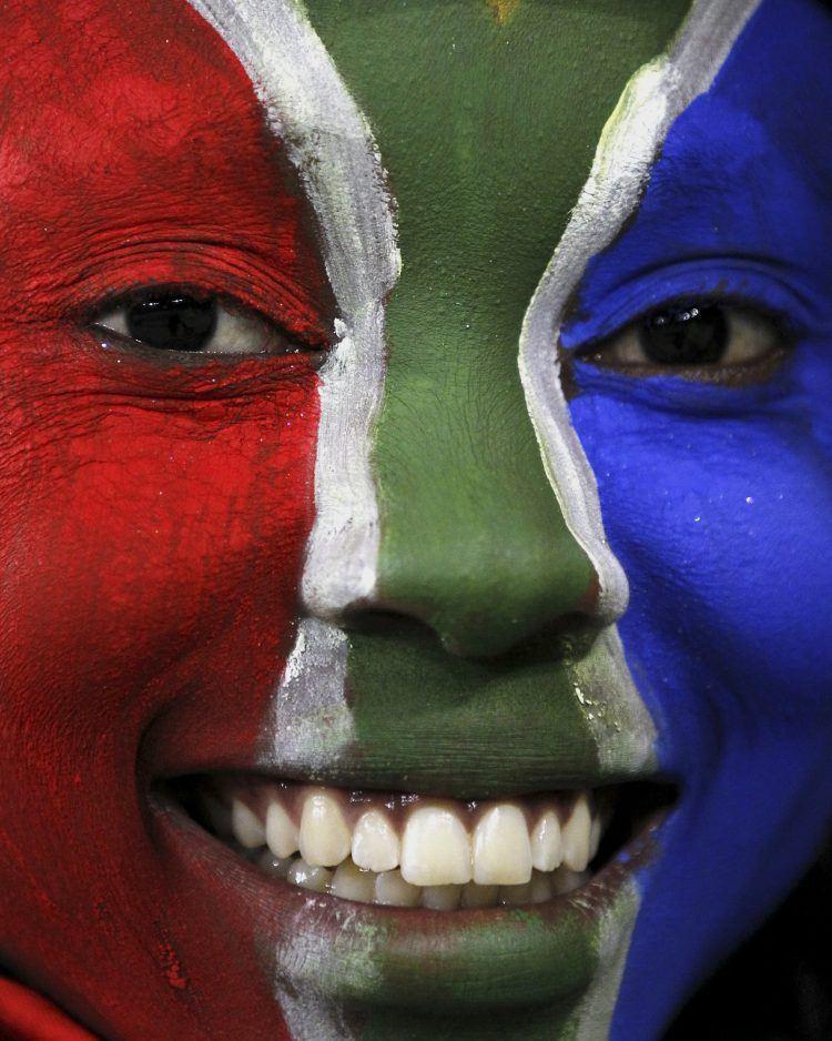 Frau mit Gesichtsbemalung in den Farben der südafrikanischen Flagge
