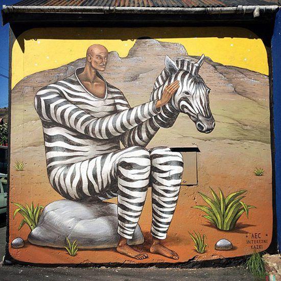 Mann in Zebrakostüm sitzt auf einem Stein - Straßenkunst in Kapstadt