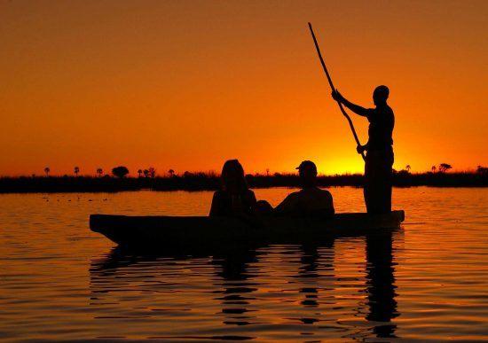 Silhueta de canoa ao pôr do sol no Delta do Okavango