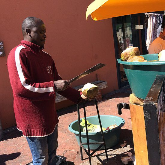 Homem corta coco em barraca no Old Biscuit Mill, Cape Town