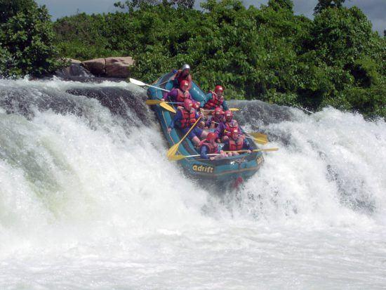 Eine Gruppe mit roten Helmen stürtzt sich beim Rafting in Uganda eine Stromschnelle hinunter