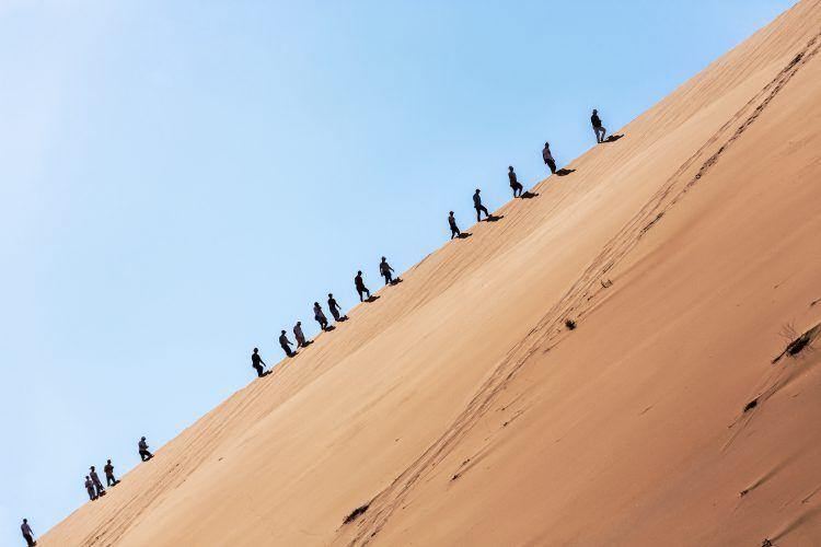 Ascension par des touristes des dunes de Sossusvlei dans le désert Namibien.