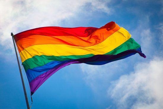 Die Regenbogenflagge weht im Wind vor blauem Himmel mit weißen Wolken