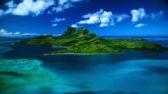 Die grüne Insel Mauritius im dunkelblauen Meer aus der Vogelperspektive