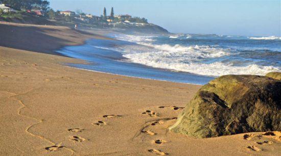 Fußspuren im Sand mit dem blauen Ozean und der Küste von Durban im Hintergrund