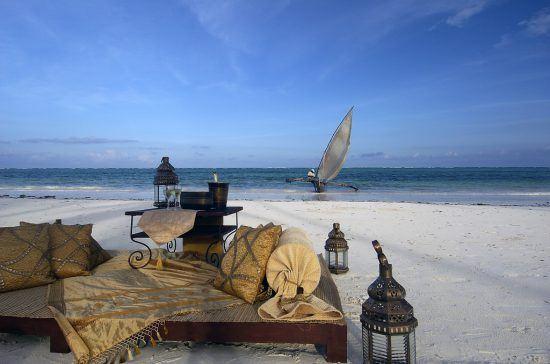 Gemütliche Sitzecke an einem Strand auf Sansibar mit einem traditionellen Segelboot im Hintergrund