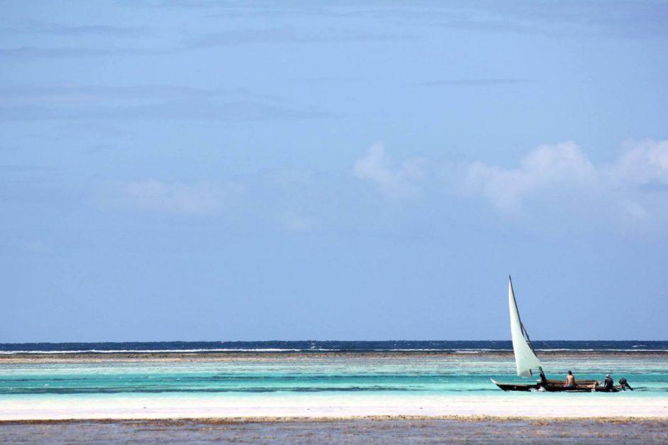 Weißer Sandstrand und dahinter türkisblaues Meer sowie ein Dhow