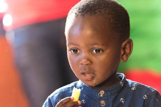 Food for Africa: Kleiner Junge aus Südafrika isst etwas