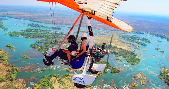 Zwei Personen fliegen in einem Ultraleichtflugzeug über die Victoria-Fälle in Sambia