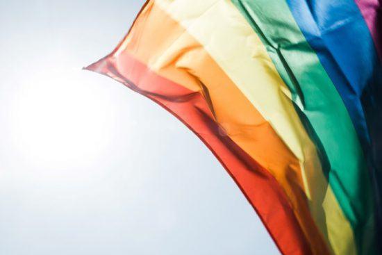 Eine Regenbogenflagge weht in der Sonne
