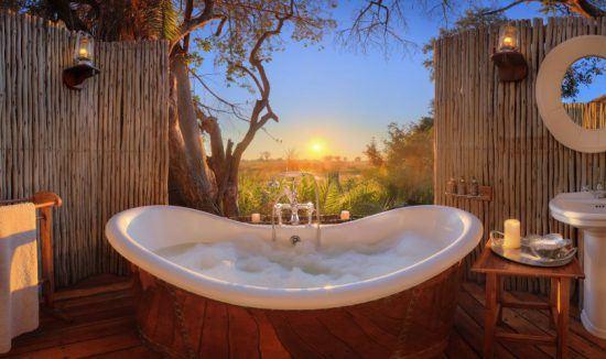 Badewanne im Freien mit Blick auf den Sonnenuntergang über dem afrikanischen Busch