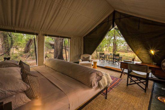 Ein offenes Zelt mit Doppelbett mitten in der Wildnis - die schönsten Unterkünfte in Botswana