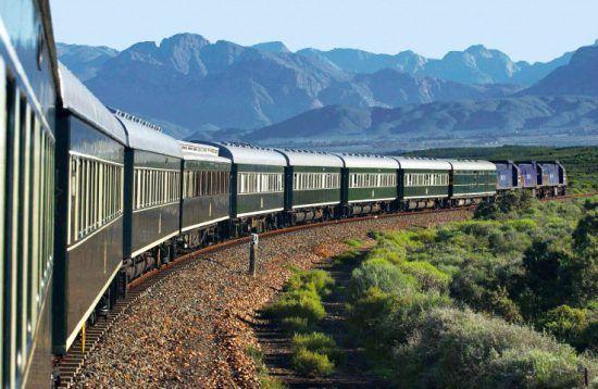 Der grüne Rovos Rail schlängelt sich durch eine malerische Berglandschaft
