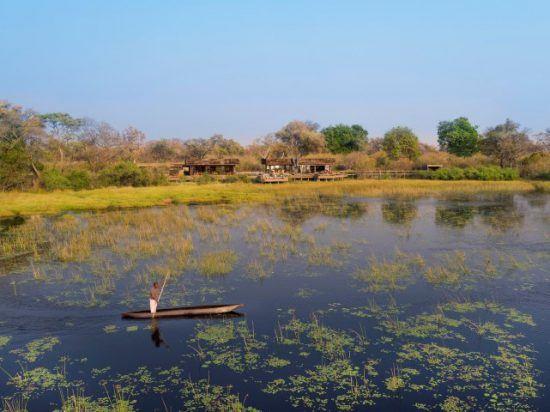 Okavango-Delta-Safari: Ein Mann in einem traditionellen Kanu gleitet vor einer Lodge über das Wasser des Okavango Delta