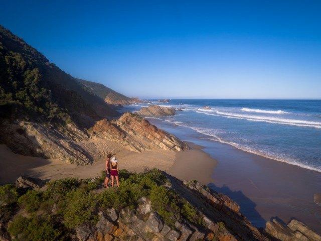 Die romantischsten Orte an der Garden Route: Ein Paar steht auf einem Hügel und blickt auf einen wunderschönen Strand