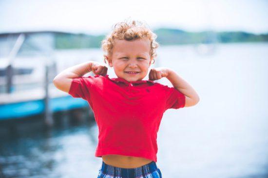 Ein Junge in einem pinken Shirt präsentiert seine Muskeln vor einem Bootsanleger