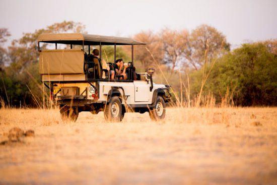 Fotografen auf einer Safari in einem offenen Geländewagen im afrikanischen Busch