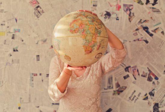 Person hält einen Globus vors Gesicht