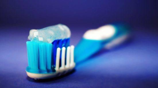 Eine blau-weiße Zahnbürste mit Zahncreme