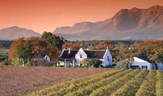 Kapholländisches Haus im herbstlichen Kapweinland bei Abendröte - beste Reisezeit für Kapstadt und den Krüger Nationalpark