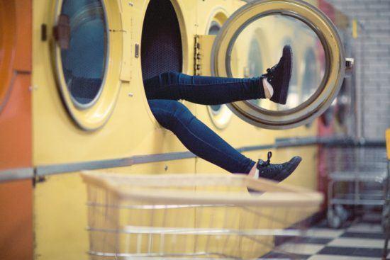 Eine Frau sitzt in einer gelben Waschmaschine im Waschsalon, sodass man nur ihre Beine sieht