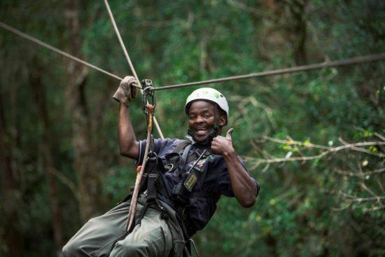 Ein Mann hebt den Daumen beim Ziplining im Wald an der Garden Route
