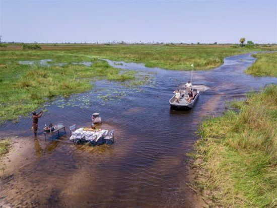 Ein Mann steht neben einem gedeckten Tisch im seichten Wasser und wartet auf ein Boot, das sich ihm nähert