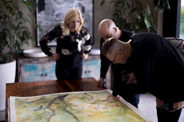 Les trois artistes impliqués dans la création des aquarelles signant leurs oeuvres.