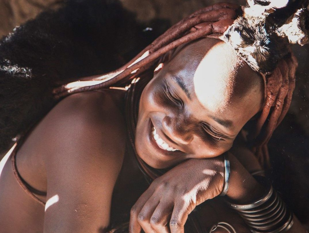 a-himba-woman-sititng-and-laughing-in-the-sunlight-namibia
