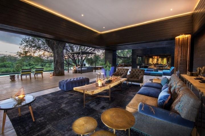 Das luxuriöse Interieur eines Gemeinschaftsraums mit Blick durch die offenen Türen hinaus in die Natur