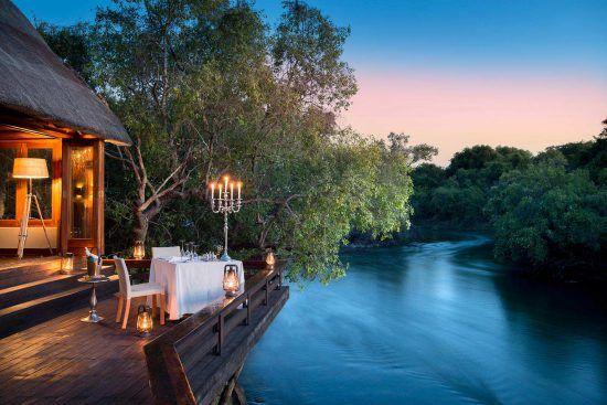 Die Royal Chundu Zambezi Island Lodge mit abendlicher Beleuchtung bei Sonnenuntergang