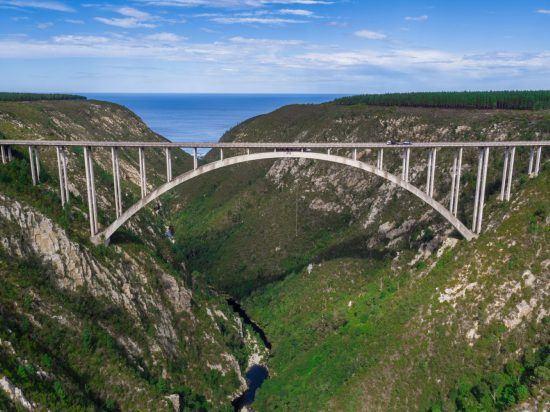 Eine Brücke, darunter führt ein Fluss richtung Meer