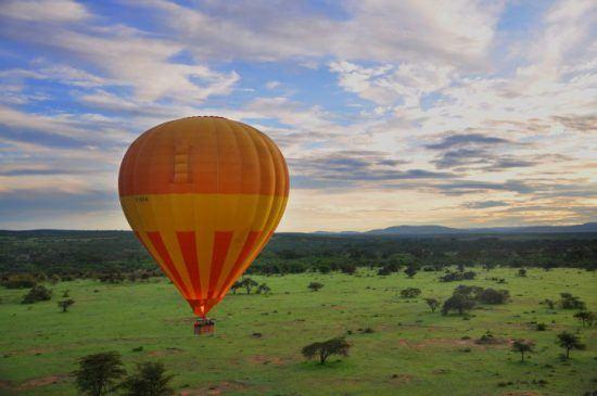 Ein gelb-orangener Heißluftballoon fliegt über den Krüger Nationalpark