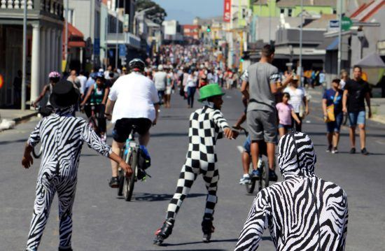 Verkleidete Menschen auf Fahrrädern und Rollschuhen