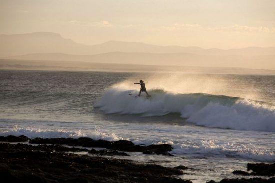 Ein Surfer beim Wellenreiten vor der Küste bei untergehender Sonne