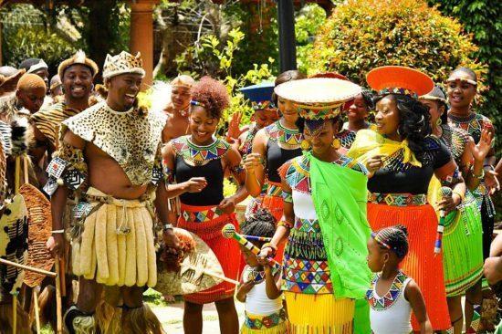 Zulus feiern eine traditionelle Hochzeit, vier Menschen im Vodergrund sind sehr bunt gekleidet