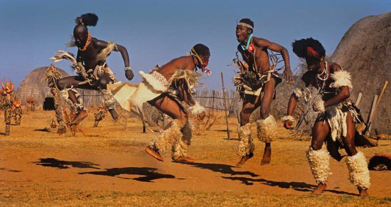 Vier Zulu-Männer führen einen traditionellen Tanz auf
